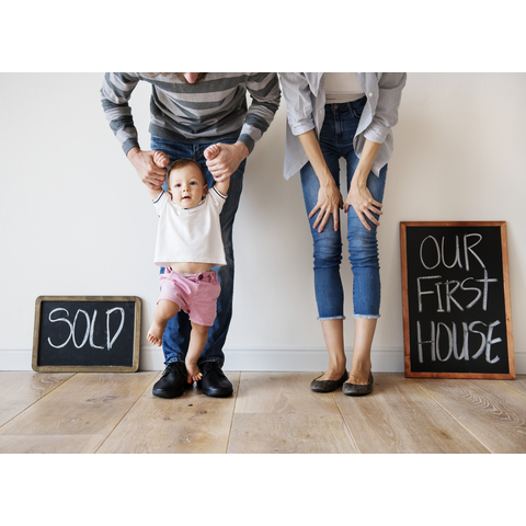 Family standing with baby with house sold sign