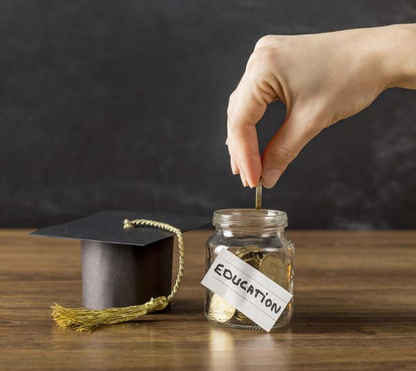 Hand putting money in jar saving for college