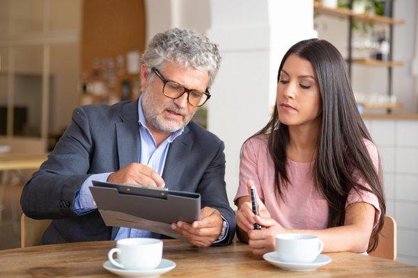 Financial advisor explaining finances to young woman
